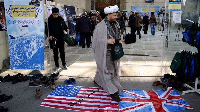 An Iranian cleric walking over British and US flags Pic: Shutterstock