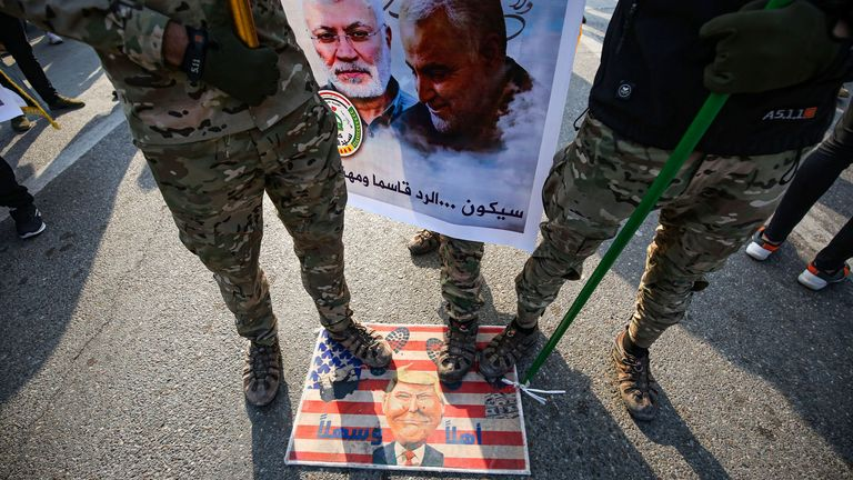 Protesters stand on a makeshift US flag bearing a caricature of President Donald Trump