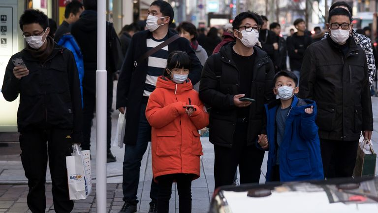 Chinese tourists wearing masks walk through the Ginza shopping district in Tokyo, Japan