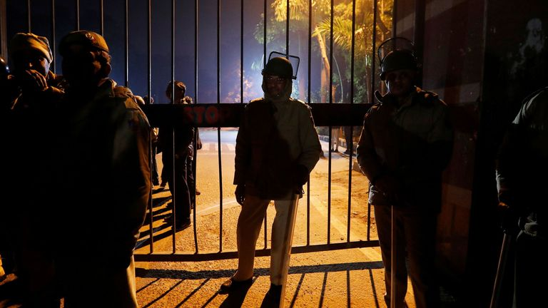 Police in riot gear stand guard outside the Jawaharlal Nehru University