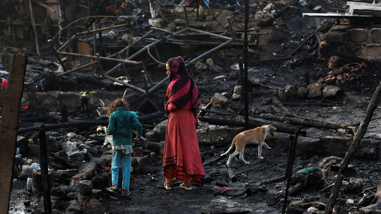 Children look for possessions at their the burnt-out house