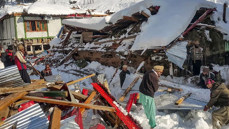Workers clear the destruction in the path of the avalanches