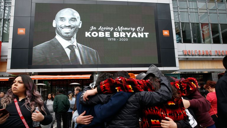 Fans gather near an image of Kobe Bryant shown on a large screen outside the Staples Center, LA