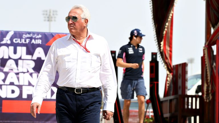 Owner of Racing Point Lawrence Stroll walks in the Paddock followed by son Lance Stroll of Canada