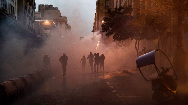 Anti-government protesters walk through clouds of tear gas during clashes with security forces in the central downtown district of the Lebanese capital near the parliament headquarters on January 18, 2020. (Photo by Anwar AMRO / AFP) (Photo by ANWAR AMRO/AFP via Getty Images)