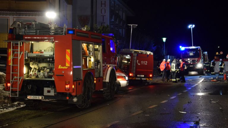 Firefighters attend to the scene where a male driver of a car hit a group of German tourists