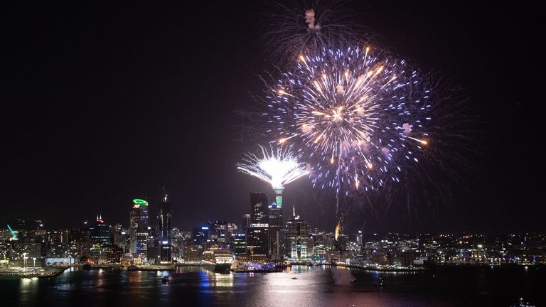 Fireworks explode from Auckland's Waitemata Harbour and Sky Tower