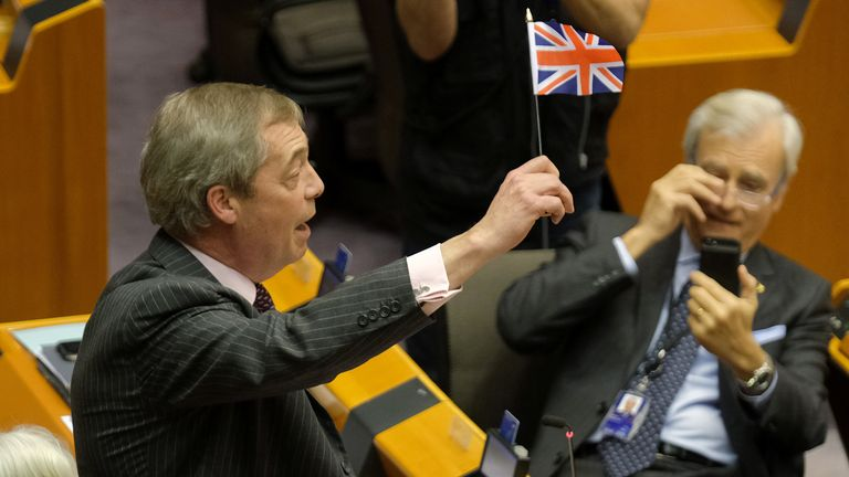 Brexit Party leader Nigel Farage waves a British flag while speaking at a session of the European Parliament