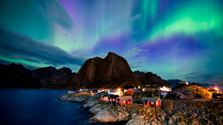Northern lights (aurora borealis) illuminate the sky over Reinfjorden in Reine, on Lofoten Islands, Norway, Arctic Circle, on September 8, 2017