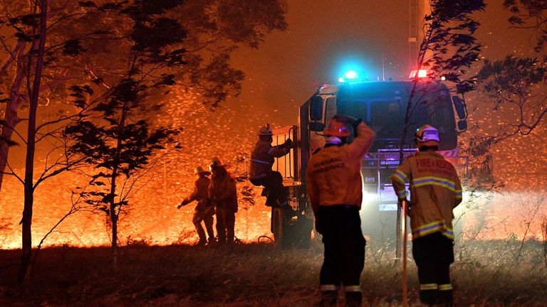 Firefighters hose down trees as they battle against bushfires around the town of Nowra in the Australian state of New South Wales on December 31, 2019