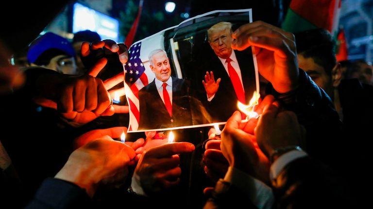 Palestinians burn a photo of Benjamin Netanyahu and Donald Trump