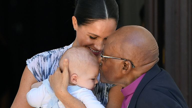 Baby Archie is kissed on the forehead by Archbishop Desmond Tutu