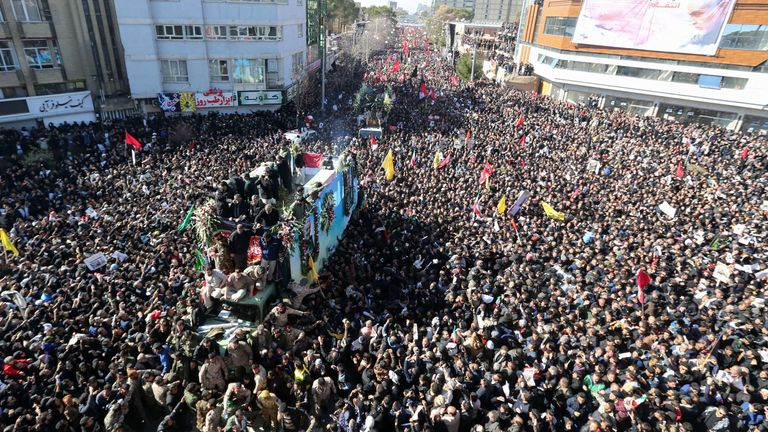 Iranian mourners gather around a vehicle carrying the coffin of Qassem Soleimani
