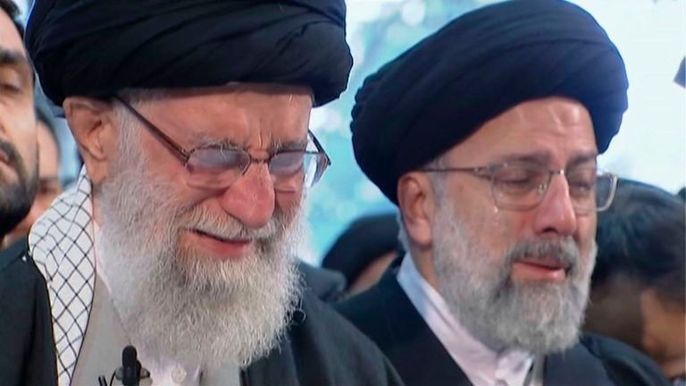 Iranian Supreme Leader Ayatollah Ali Khamenei, left,nweeps as he leads a prayer over the coffin of Gen. Qassem Soleimani