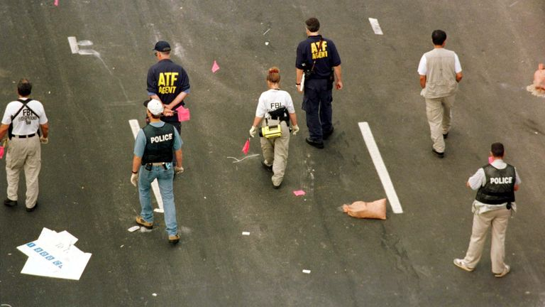 Alcohol, Tobacco and Firearms agents, FBI agents and local police officers carry red flags to mark evidence in their investigation of a suspected pipe bomb blast which exploded in Centennial Olympic Park in Atlanta, early July 27 1996