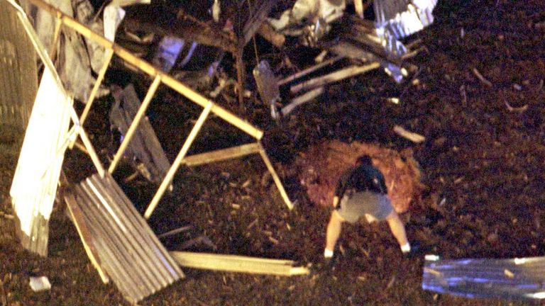 A law enforcement officer peers into the crater caused by a bomb blast in Atlanta's Centennial Olympic Park early July 27, tearing apart an audio tower at rear and killing at least two people and injuring dozens