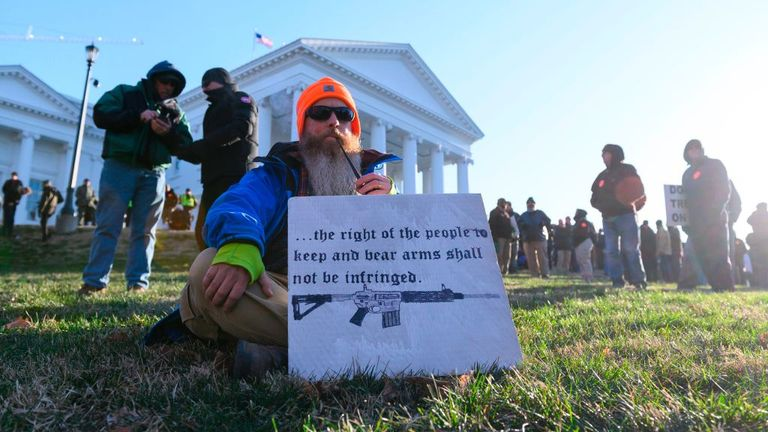 A pro gun supporter smokes a pipe while displaying a sign as he waited for a rally to begin on the grounds of the Virginia State Capitol