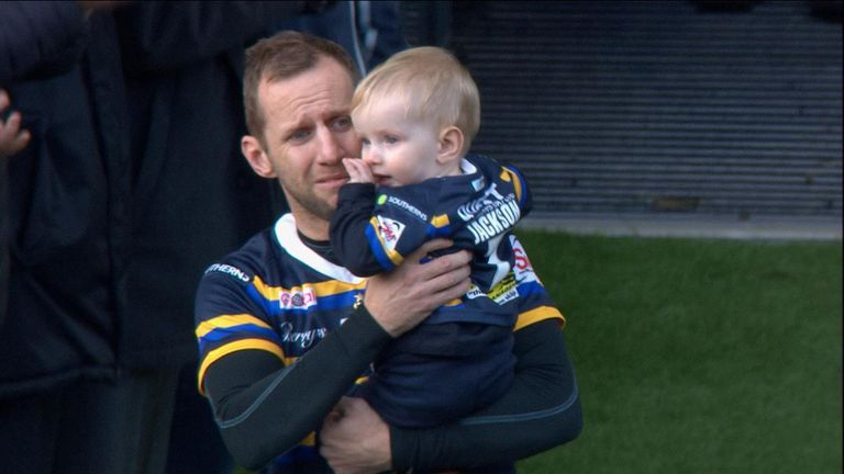 Rob Burrow carries his son Jackson onto the field at his testimonial