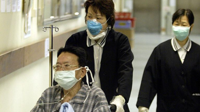 A patient is wheeled through the Prince of Wales hospital wearing masks to guard against a mysterious outbreak of pneumonia which has hit Hong Kong in the last week, 19 March 2003. A second man has died with 111 people struck down in the territory after contracting the mysterious pnemonia called Severe Acute Respiratory Syndrome (SARS) which is suspected to have claimed the lives of at least 11 people in Asia and Canada.