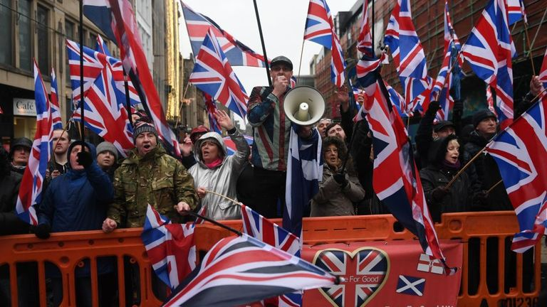Unionist counter-demonstrators waving Union Flags oppose pro-independence marchers in Glasgow on January 11, 2020. - Thousands of independence supporters were expected the march through the streets of Glasgow, despite a rally that was planned to conclude the event being cancelled after Met Office warnings of high winds. (Photo by ANDY BUCHANAN / AFP) (Photo by ANDY BUCHANAN/AFP via Getty Images)
