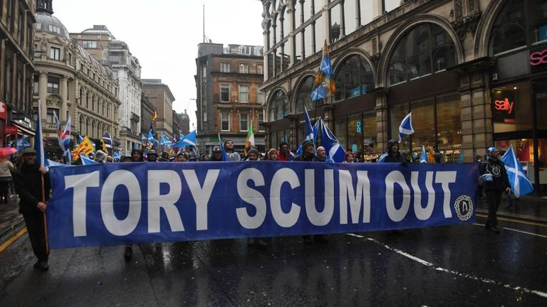 """Pro-independence protester holds up a long banner that reads """"Tory scum out"""" during a march organised by the grassroots organistaion All Under One Banner calling for Scottish independence in Glasgow on January 11, 2020. - Thousands of independence supporters are expected the march through the streets of Glasgow, despite a rally that was planned to conclude the event being cancelled after Met Office warnings of high winds. (Photo by ANDY BUCHANAN / AFP) (Photo by ANDY BUCHANAN/AFP via Getty Image"""