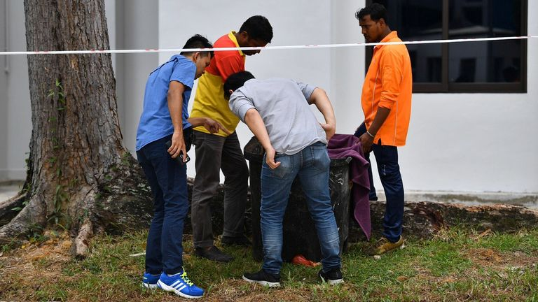 Police officers and cleaners inspect the contents of a bin at a rubbish chute, after a baby was found alive among rubbish in the bin at a public housing estate in Singapore. Pic: Lim Yaohui/The Straits Times