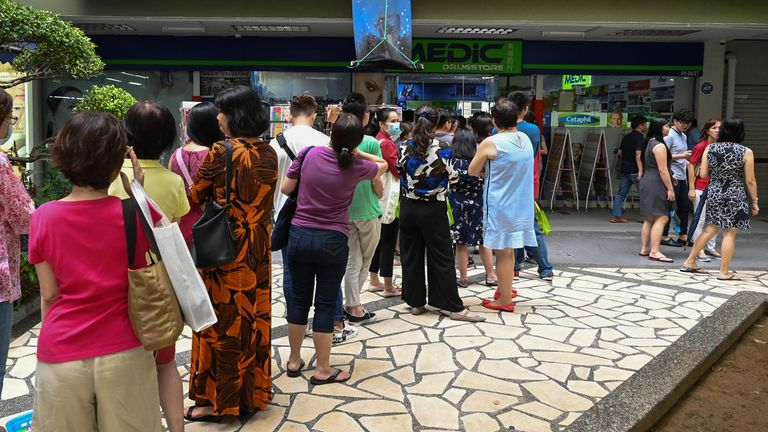 Queues for protective masks at a drugs store in Singapore