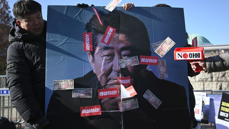 South Korean protesters hold a banner showing a picture of Japan's Prime Minister Shinzo Abe