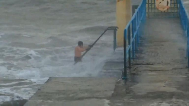 Swimmer struggles to emerge from rough sea