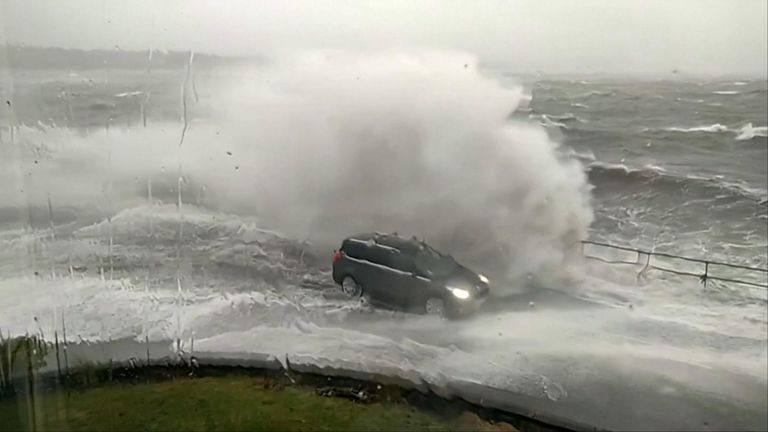 Eyewitness footage shows waves splashing over cars on coastal road in the west of Scotland.