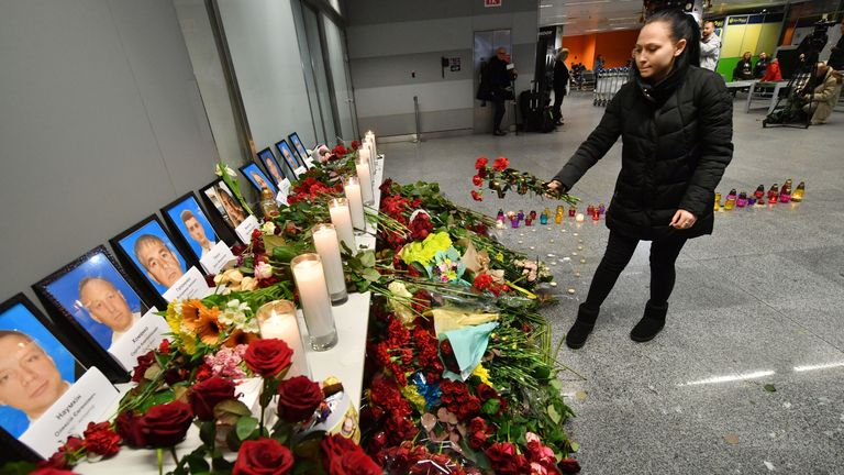 A woman places flowers at a memorial for the victims of the plane crash in Tehran