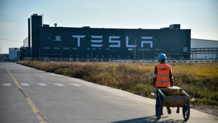 A worker walks on a road next to the new Tesla factory built in Shanghai on November 8, 2019. (Photo by HECTOR RETAMAL / AFP) (Photo by HECTOR RETAMAL/AFP via Getty Images)