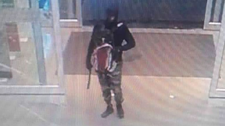 Suspect wearing balaclava, camouflage pants and carrying a handgun with suppressor attached, as they arrive to rob a gold shop inside a department store in Lopburi province, Thailand