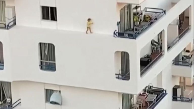 This is the moment a toddler was filmed climbing out of a window and walking along a narrow ledge on the fourth floor of a hotel.