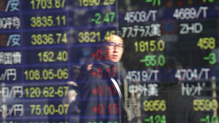 A man is seen reflected as he looks at a stock indicator showing share prices of Japanese companies in Tokyo on January 6, 2020