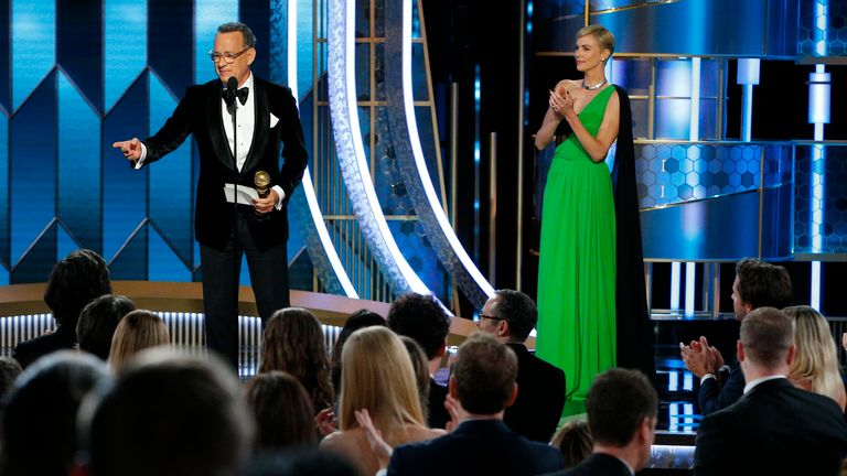 Tom Hanks accepts his lifetime achievement award at the Golden Globes from Charlize Theron