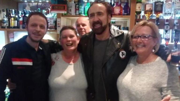 Nicholas Cage poses for a photo behind the bar. Pic: Tramways Social Club