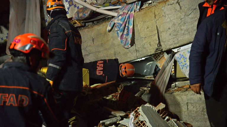 Turkish officials and police work at the scene of a collapsed building following a 6.8 magnitude earthquake in Elazig