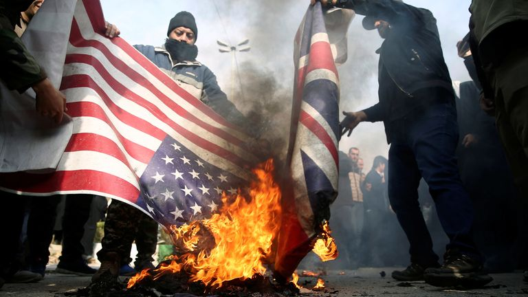 Protesters burn the US and British flags during a protest against killing of Iranian Major General Qassem Soleimani