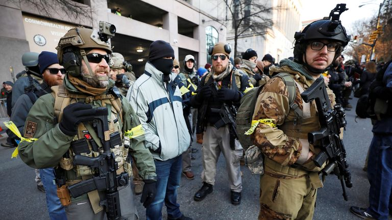 Armed militia members stand guard outside a no-gun zone at a rally by gun rights advocates and militia members near Virginia's Capitol, in Richmond