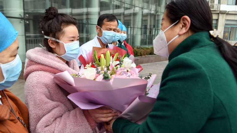 A woman (L), who recovered after being infected by a new coronavirus, receives a bouquet as she walks out of a hospital in Bozhou, in China's eastern Anhui province on January 29, 2020
