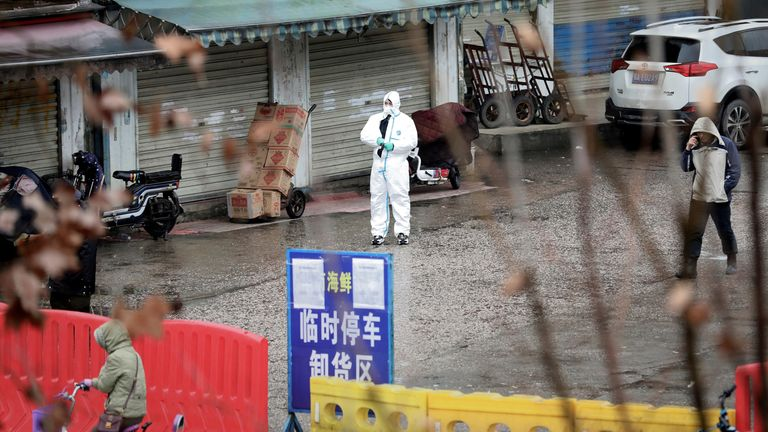 A worker in a protective suit stands outside the closed Wuhan seafood market