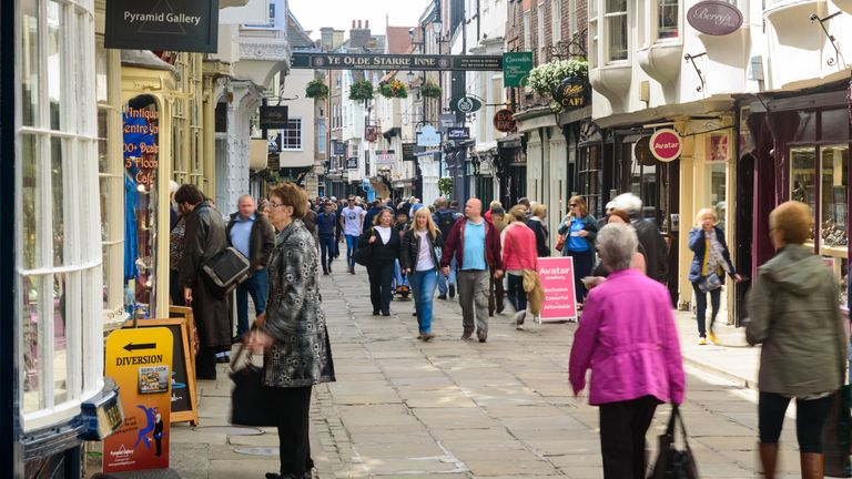 Tourists visiting and shopping in York's popular Stonegate shopping street
