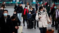 Mask-wearing passengers are seen leaving Beijing railway station