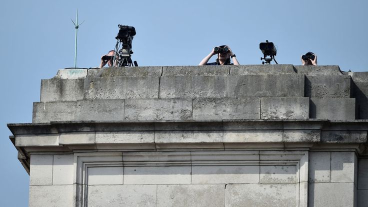Security personnel use binoculars from the rooftop of Buckingham Palace, before the departure of Britain's Queen Elizabeth to the Houses of Parliament for the State Opening of Parliament in London on June 21, 2017. Queen Elizabeth II will formally open parliament and announce the British government's legislative programme on Wednesday, two days later than planned. The state opening, a ceremony full of pomp in which the monarch reads out the Queen's Speech detailing the government's programme for