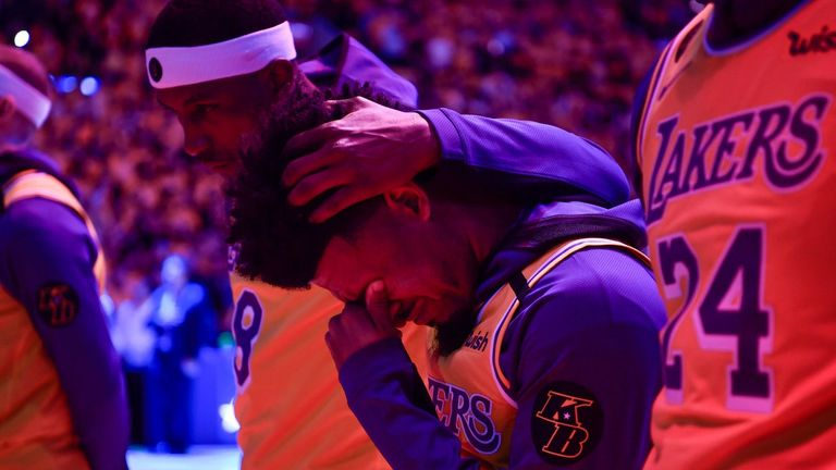 Jan 31, 2020; Los Angeles, California, USA; Los Angeles Lakers guard Quinn Cook is overcome with emotion and is comforted by teammate Los Angeles Lakers guard Kentavious Caldwell-Pope during the national anthem before playing the Portland Trail Blazers at Staples Center. The team held a memorial tribute for longtime guard Kobe Bryant who died in. A helicopter crash January 26, 2020. Mandatory Credit: Robert Hanashiro-USA TODAY Sports