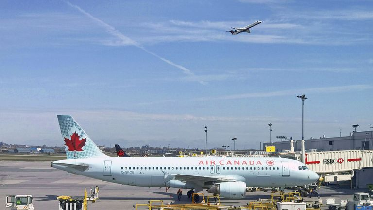(FILES) In this file photo taken on May 1, 2018 an Air Canada plane sits on the tarmac at Trudeau airport near Montreal, Canada. - A woman boarded an Air Canada flight earlier in June 2019, fell asleep after takeoff and woke up alone in a dark, parked plane, apparently forgotten about by ground staff. Tiffani Adams's story was posted by a friend on Air Canada's Facebook page, drawing incredulous reactions from readers and a request for details from the airline.According to the post, Adams was flying from Quebec to Toronto Pearson International Airport when she fell asleep, aided by the fact that she'd ended up with a whole row of seats to herself. (Photo by Daniel SLIM / AFP) (Photo credit should read DANIEL SLIM/AFP via Getty Images)