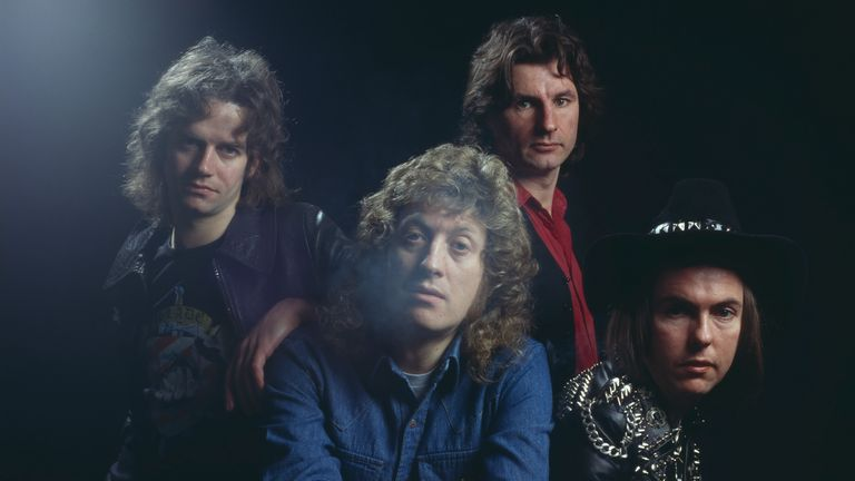 Studio portrait of English rock group Slade, posed in London circa 1975. Clockwise, from front: singer Noddy Holder, bassist Jim Lea, drummer Don Powell and guitarist Dave Hill wearing leather jacket with metal studs. (Photo by Michael Putland/Getty Images)