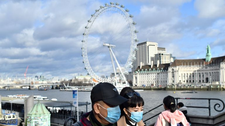 A couple wear face masks as they walk along the Thames embankment in central London on January 28, 2020. - Around 1,500 people who came to Britain from the Chinese epicentre of the coronavirus epidemic in the past two weeks must put themselves in isolation, the UK health minister has said. (Photo by Justin TALLIS / AFP) (Photo by JUSTIN TALLIS/AFP via Getty Images)
