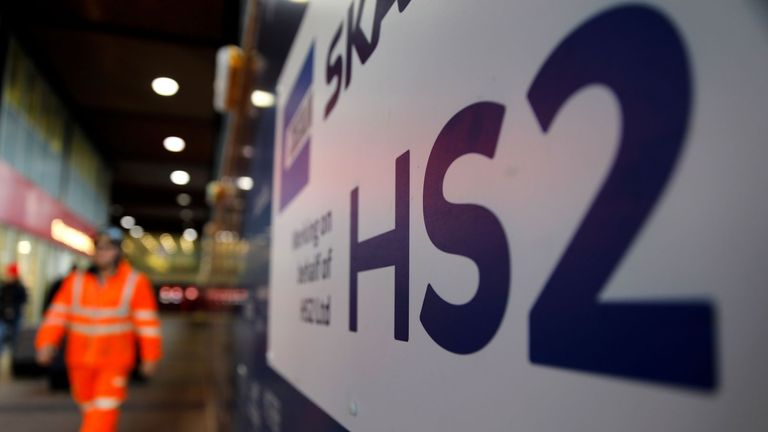 A worker walks past a sign outside a construction site for a section of Britain's HS2 high-speed railway project, at London Euston train station in London on January 20, 2020. - Britain's government on Monday said it would shortly decide on whether to proceed with its HS2 high-speed two railway project, whose cost is reportedly set to soar to more than £100 billion. HS2, which will quicken rail journeys between London in southeast England and cities to the north of the capital, has been dogged by controversy owing to projected spiralling costs and damage to wildlife. (Photo by Tolga AKMEN / AFP) (Photo by TOLGA AKMEN/AFP via Getty Images)